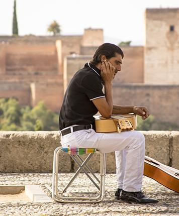 Alhambra y guitarrista flamenco en el mirador de San Nicolás en el barrio del Albaicín Granada